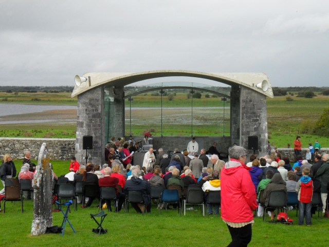 Pilgrims seated in front of the open air oratory