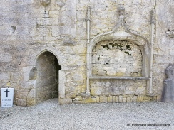 Tomb niche in south wall of chancel of church , with door leading to cloister at Askeaton Friary.
