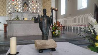 The Relic is a piece of his bone, and is contained within the rose window of a scale model of the Basilica of St. Willibrord, which a bronze statue of a young missionary St. Willibrord is holding in his right hand. He holds his crozier in his left hand. Willibrord is standing on a piece of sandstone taken from the remains of his original abbey, which is in the crypt of the Basilica